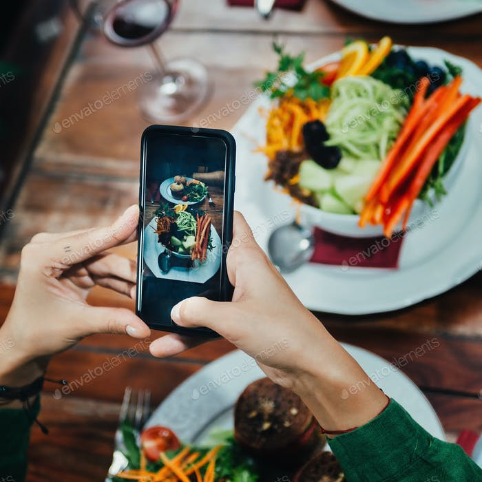 Girl Photographing Food In A Restaurant