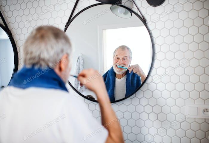 Ein Senior Mann putzt Zähne im Bad drinnen zu Hause. Kopierbereich