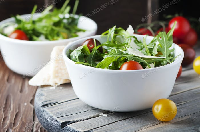 Healthy salad with rocket, tomato and parmesan cheese