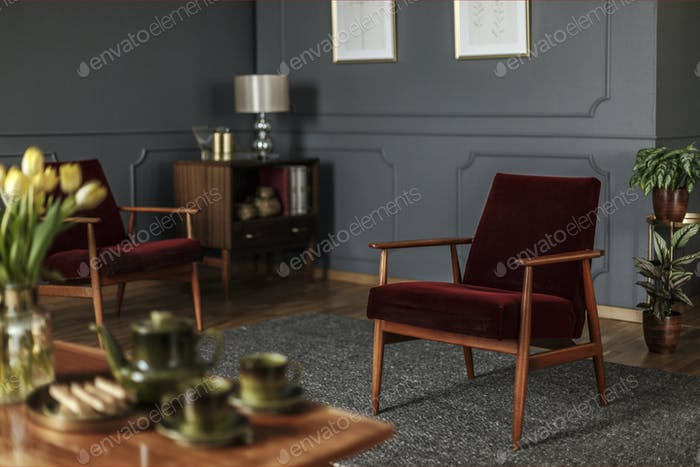 Real photo of a wine red armchair standing in the middle of an e