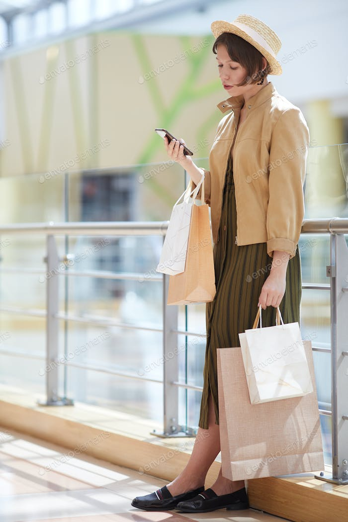 Young shopper texting on phone