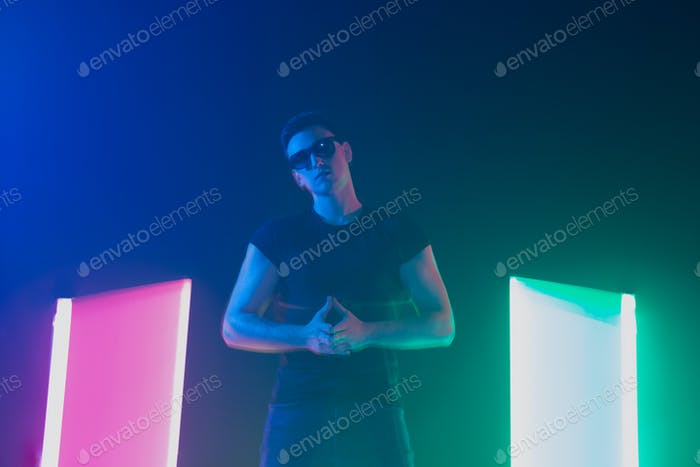 Young caucasian man posing stylish in neon light on dark background