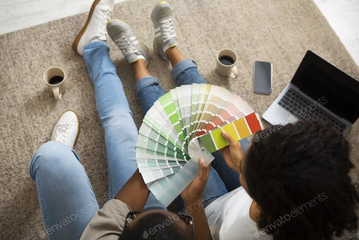 African american girl and man with color swatch in hands sitting on floor