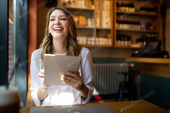 Happy girl working online or studying and learning while using tablet