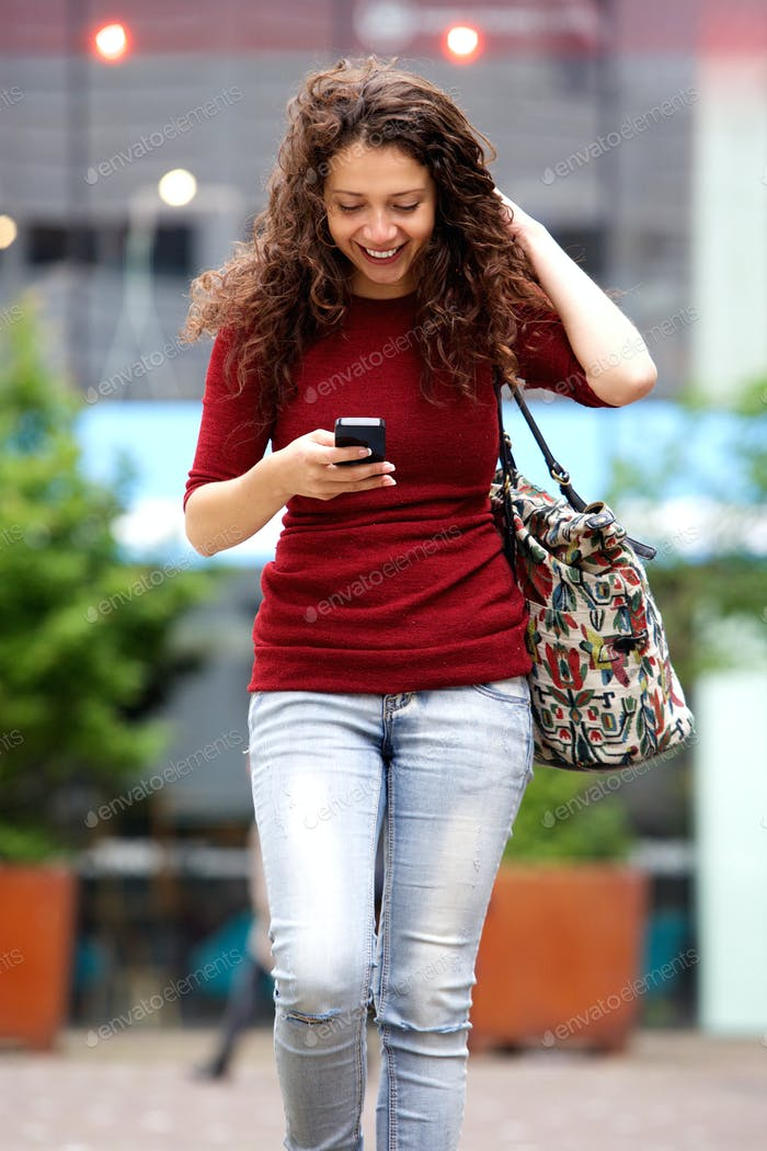 Cheerful young woman walking outdoors with mobile phone