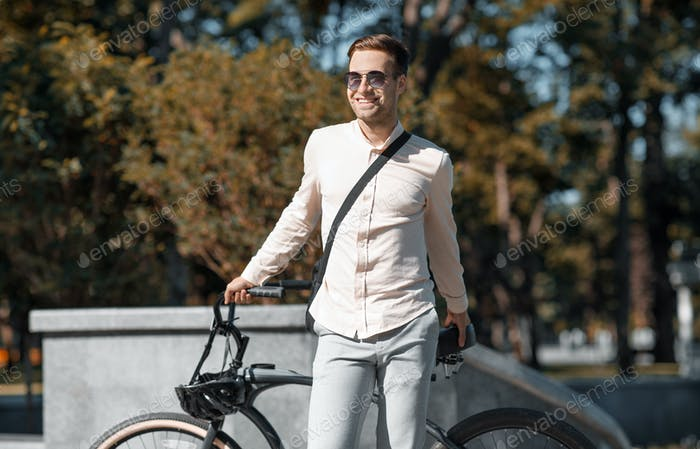 Portrait of hipster businessman in sunglasses with bicycle standing