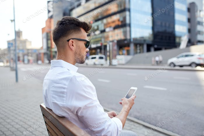 close up of man texting on smartphone in city