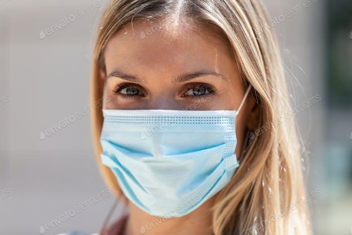 Hermosa mujer rubia con máscara protectora en la calle.