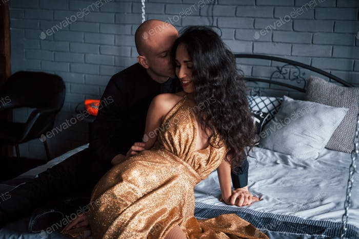 Real feelings. Couple in classic wear sits in front of the beautiful luxury decorated bed