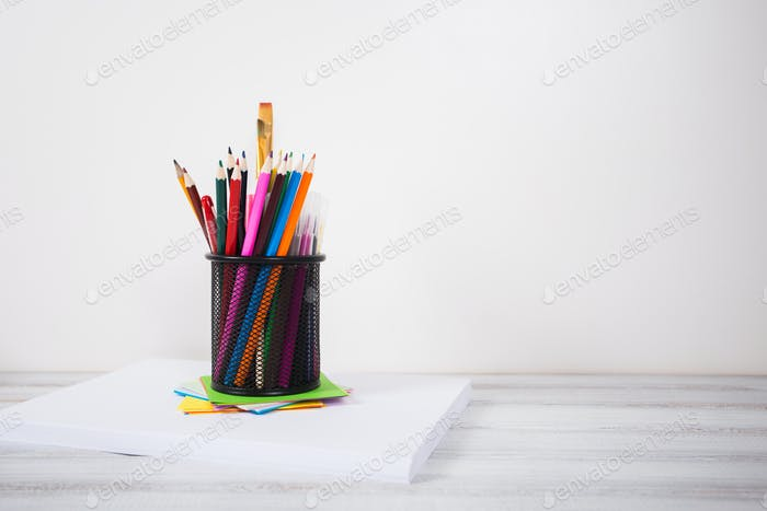 color pencils in tin can, wood table