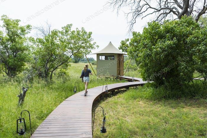 13 year old girl walking wooden path, tented camp, Botswana