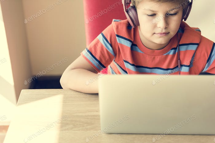 Kid Boy Headphone Using Laptop Concept