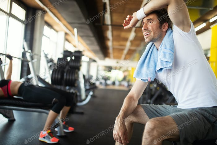 Young fit handsome man doing exercises in gym