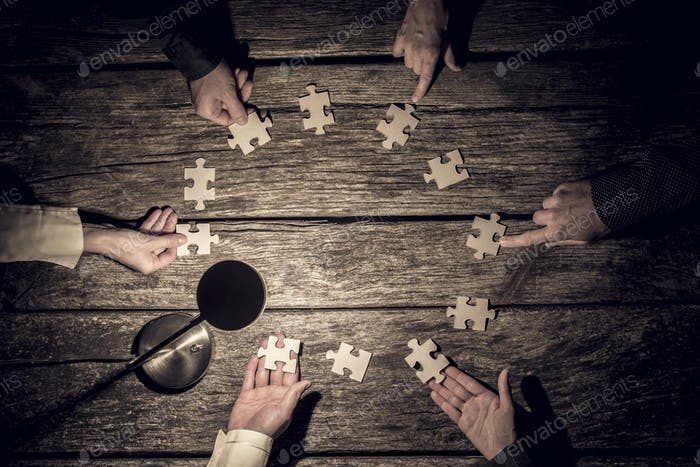 Six business partners placing puzzle pieces in a circle