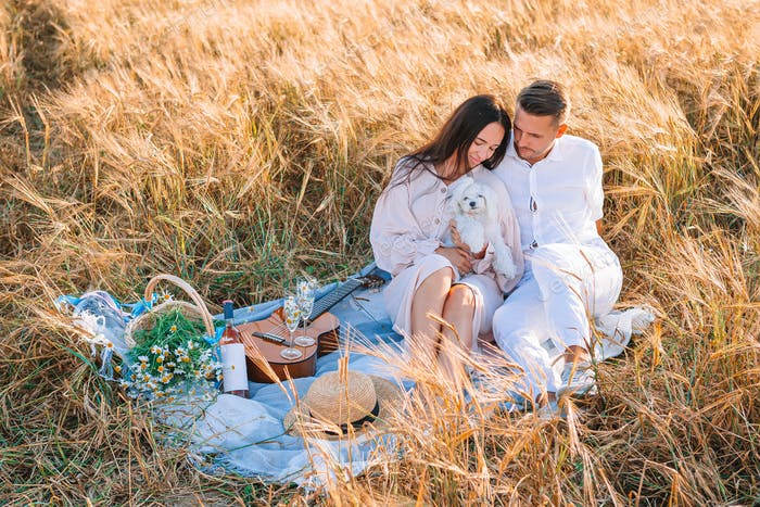 Happy young family on picnic in yellow wheat field