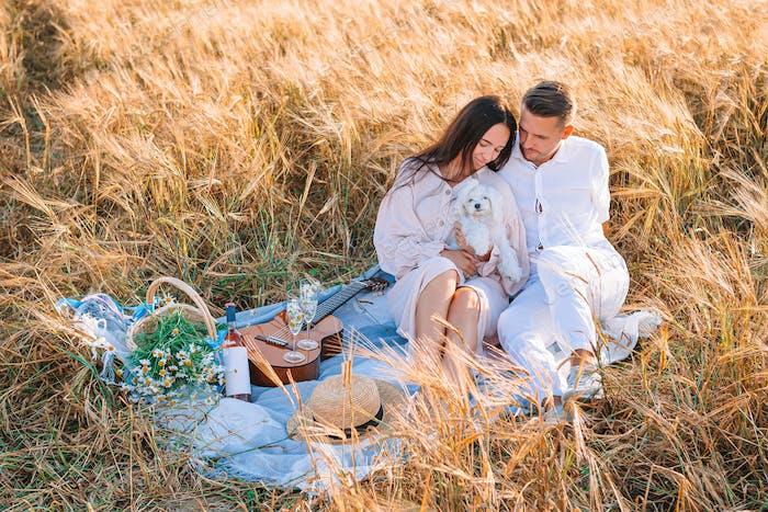 Glückliche junge Familie auf Picknick im gelben Weizenfeld