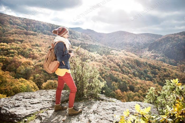 Beautiful woman with backpack against colorful sunny autumn forest