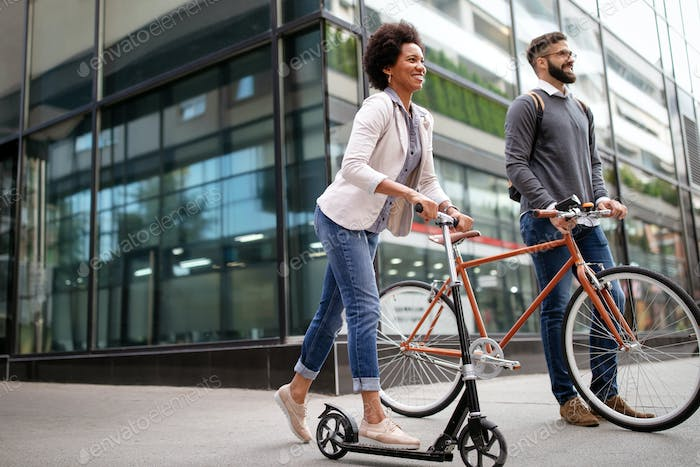 Happy couple using electric scooter, bicycle in city. Green eco energy concept with zero emission