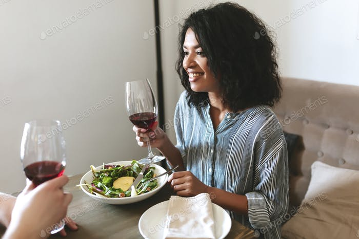 Beautiful African American girl with glass of red wine in hand and salad on table in restaurant