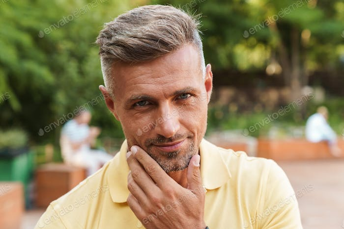 Image closeup of handsome middle-aged man touching his chin while walking in summer park