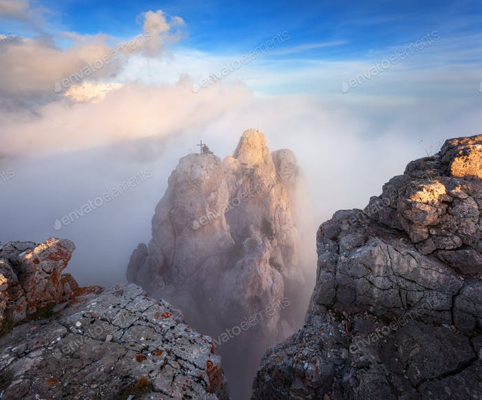 Mountain landscape. High rocks with low clouds at sunset