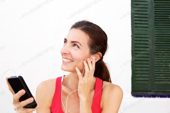 Nahaufnahme fit junge Frau entspannt mit Handy und Kopfhörer nach dem Training