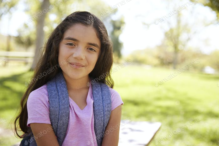 Young Hispanic schoolgirl looks to camera, smiling