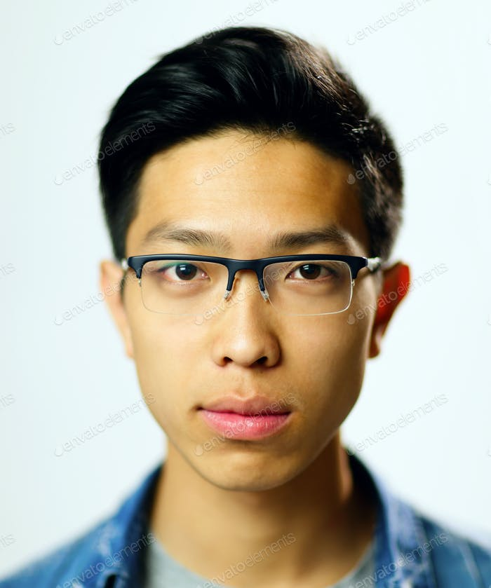 Closeup portrait of a young serious asian man on gray background