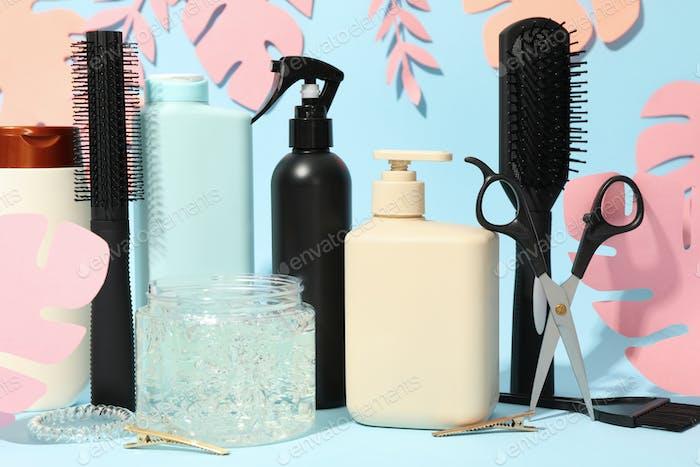 Komposition mit Friseurzubehör und Papierpalmblättern auf blauem Hintergrund