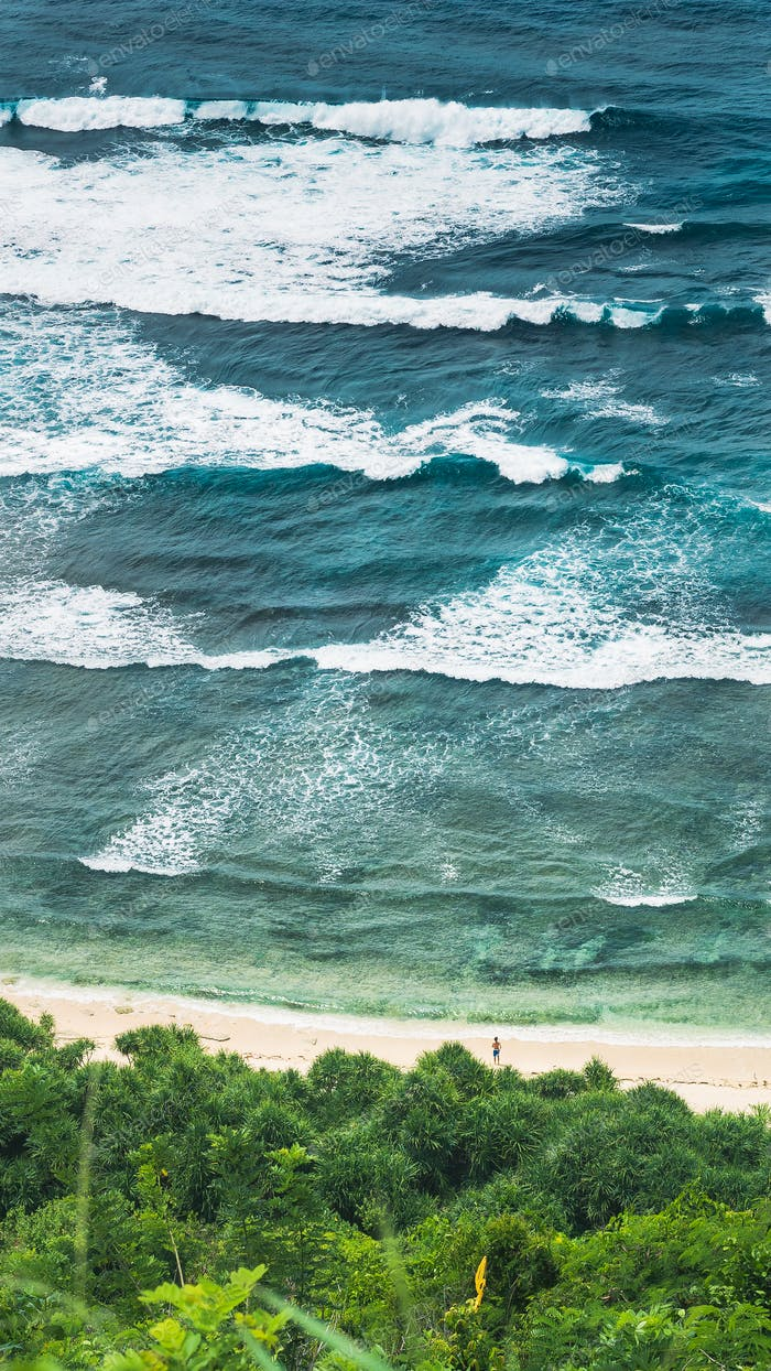 Waves Cascade and Man looking into Element on Nunggalan Beach. Uluwatu, Bali, Indonesia