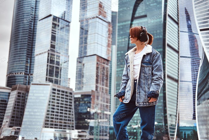 Trendy dressed hipster girl in front of skyscrapers in Moscow city at cloudy morning.