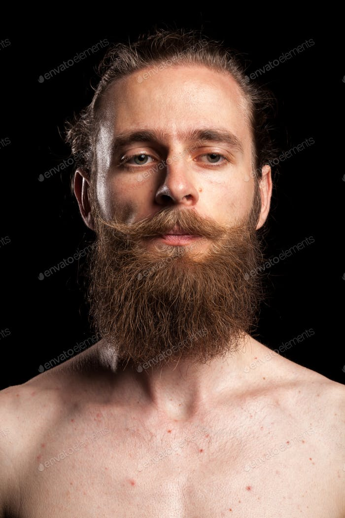 Portrait of cool tattooed bearded hipster on black background