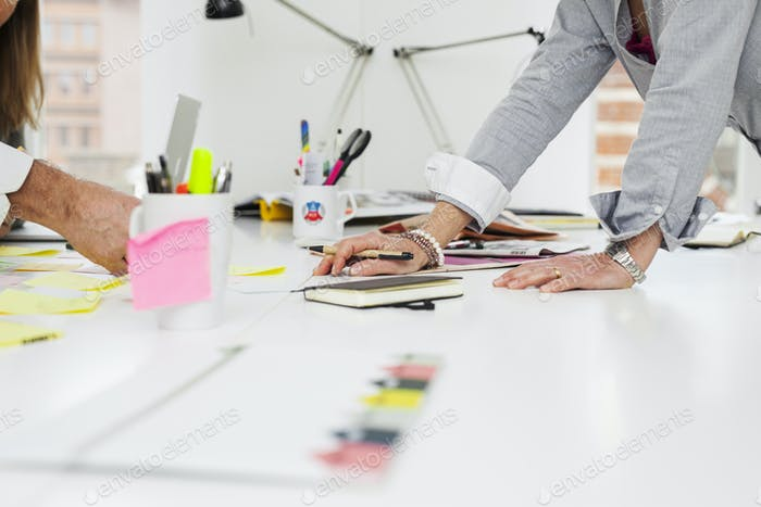Cropped image of businesspeople with adhesive notes in office