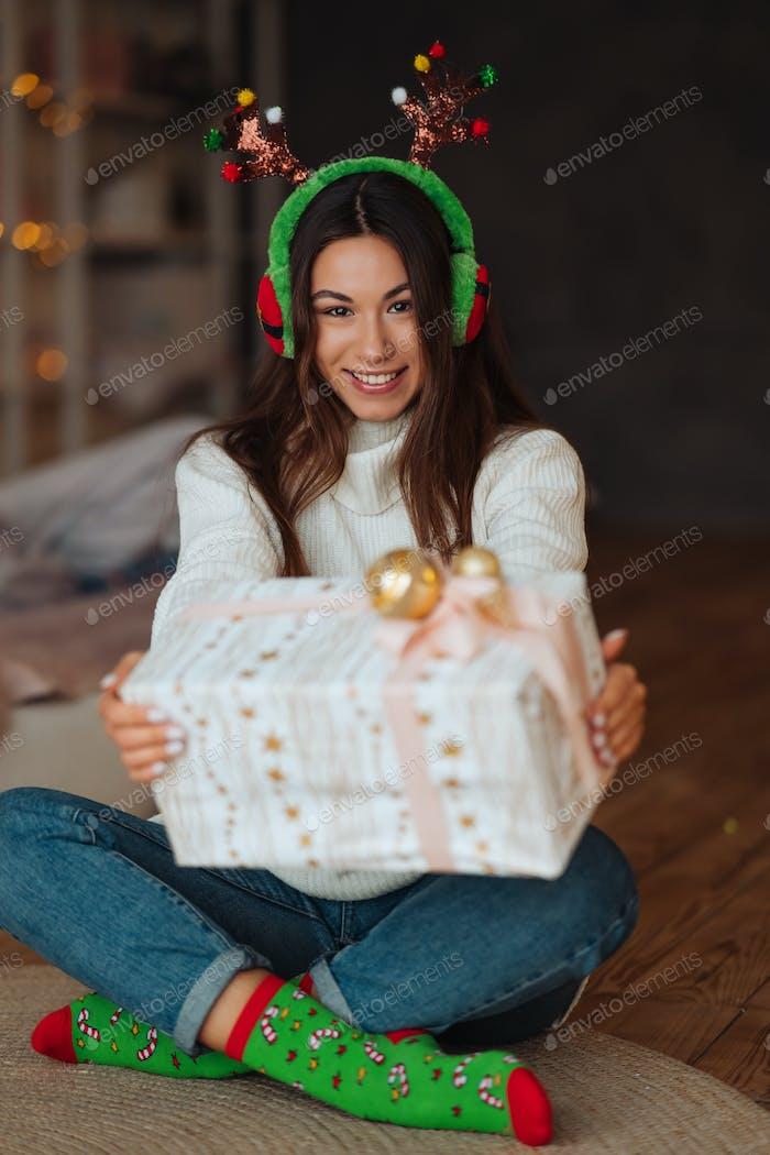 Girl with gift smiling to camera. She wearing christmas antlers