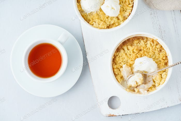 Apple crumble with ice cream, streusel. Morning breakfast with tea on a light gray table