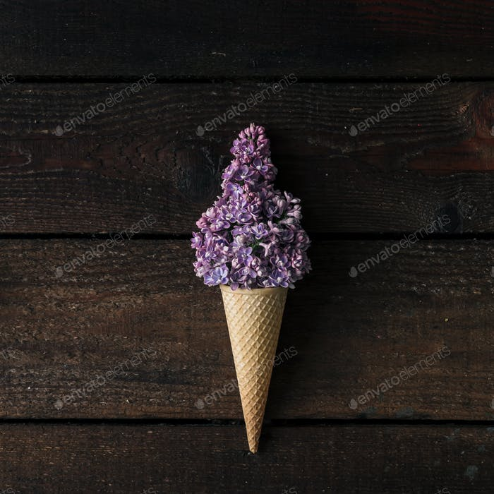 Ice cream cone with purple lilac on wooden background