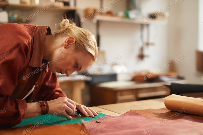 Female Artisan Cutting Leather Detail