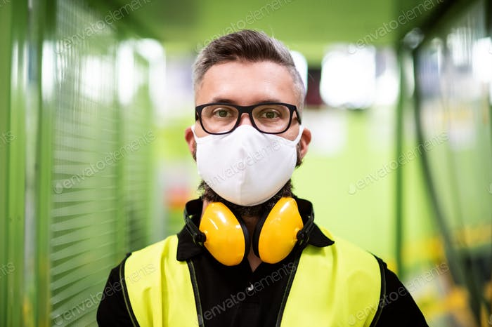 Man worker with protective mask standing in industrial factory or warehouse
