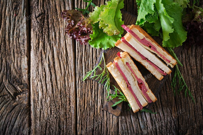 Club sandwich - panini with ham and cheese on wooden background. Picnic food. Top view. Flat lay