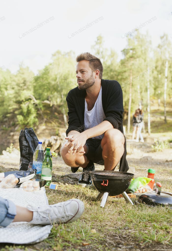 Thoughtful man crouching by barbecue grill on field