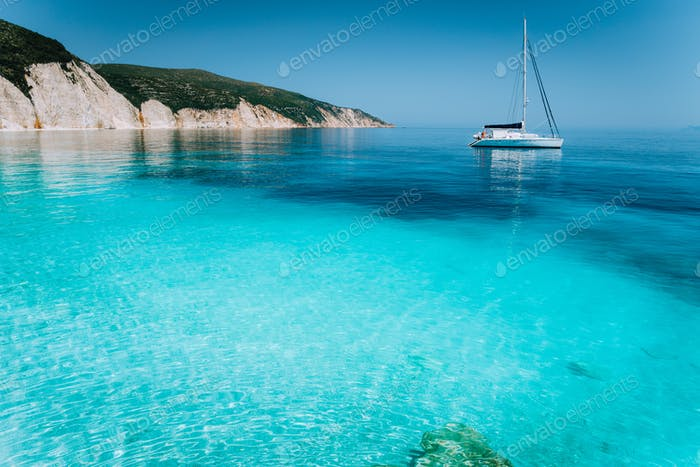 Lonely white sailing catamaran boat drift on calm sea surface. Pure shallow azure blue bay water of