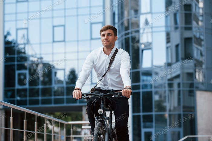 Professional politician. Businessman in formal clothes with black bicycle is in the city