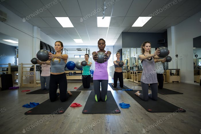 Fit women performing stretching exercise with fitness ball in gym