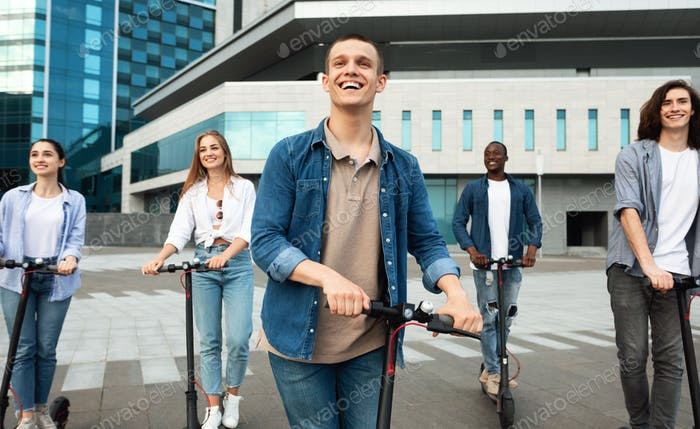Buddies having ride on motorized kick scooters