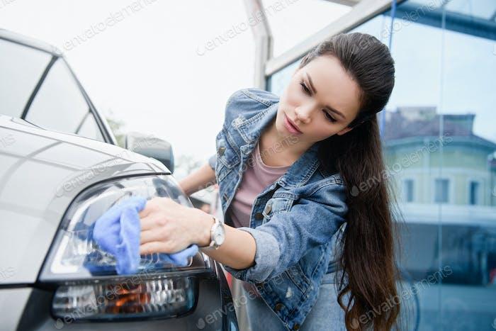 attraktive Frau reinigt Autoscheinwerfer bei Autowäsche mit Lappen