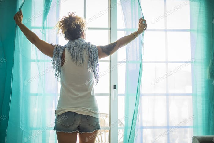beautiful caucasian woman at home alone opening a window moving the tents