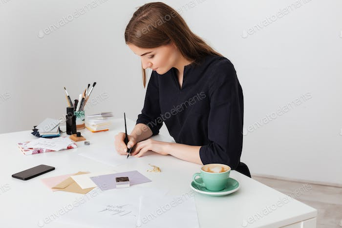 Portrait of young beautiful lady sitting at the white desk with cup of coffee and writing on paper