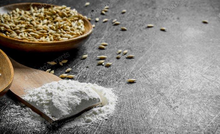 Mehl auf einem Holzspatel mit Getreide in der Schüssel.