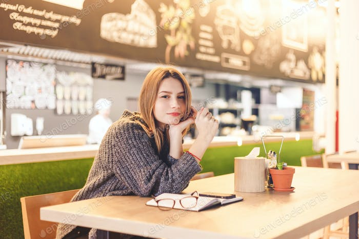Young cheerful woman posing sitting in cafe