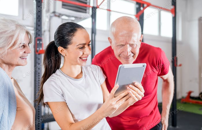 Personal trainer showing results of training on tablet to senior couple